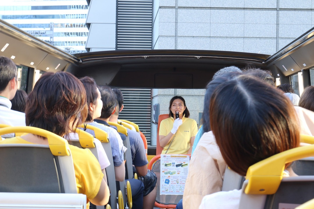 Our bus tour conductor shows us around the city in front of the bus while facing us.