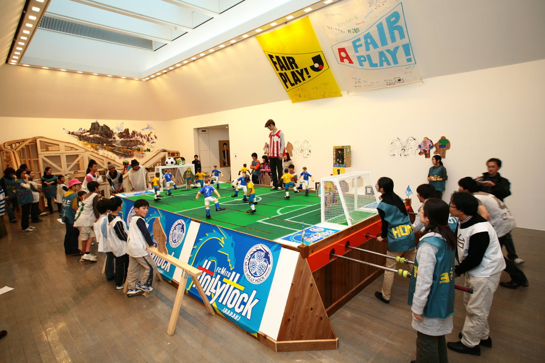 """KOSUGE1-16 """"Neighbor Land"""", where people can mix and play: Creating a place for play that crosses age and language boundaries, with attractions such as a giant soccer game and a human-powered merry-go-round."""